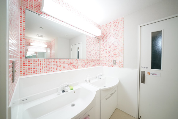 Large washroom space with cute pink and orange tiles